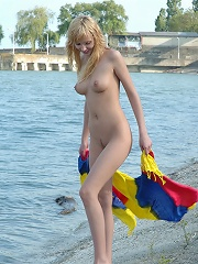 Beautiful blond sexy teen babe posing on the sea-shore